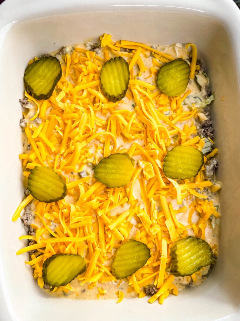 cooked ground beef in a casserole dish topped with shredded cheddar cheese and pickles