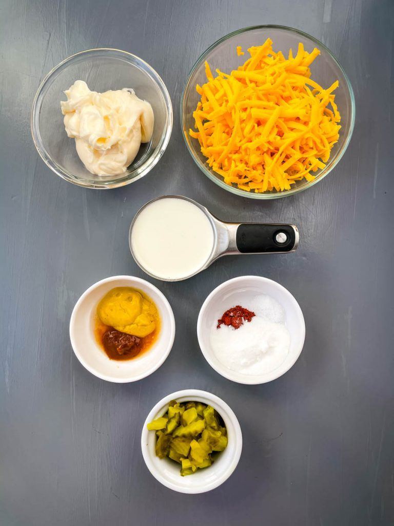 mayo, shredded cheddar, heavy cream, mustard, and chopped pickles in separate glass bowls
