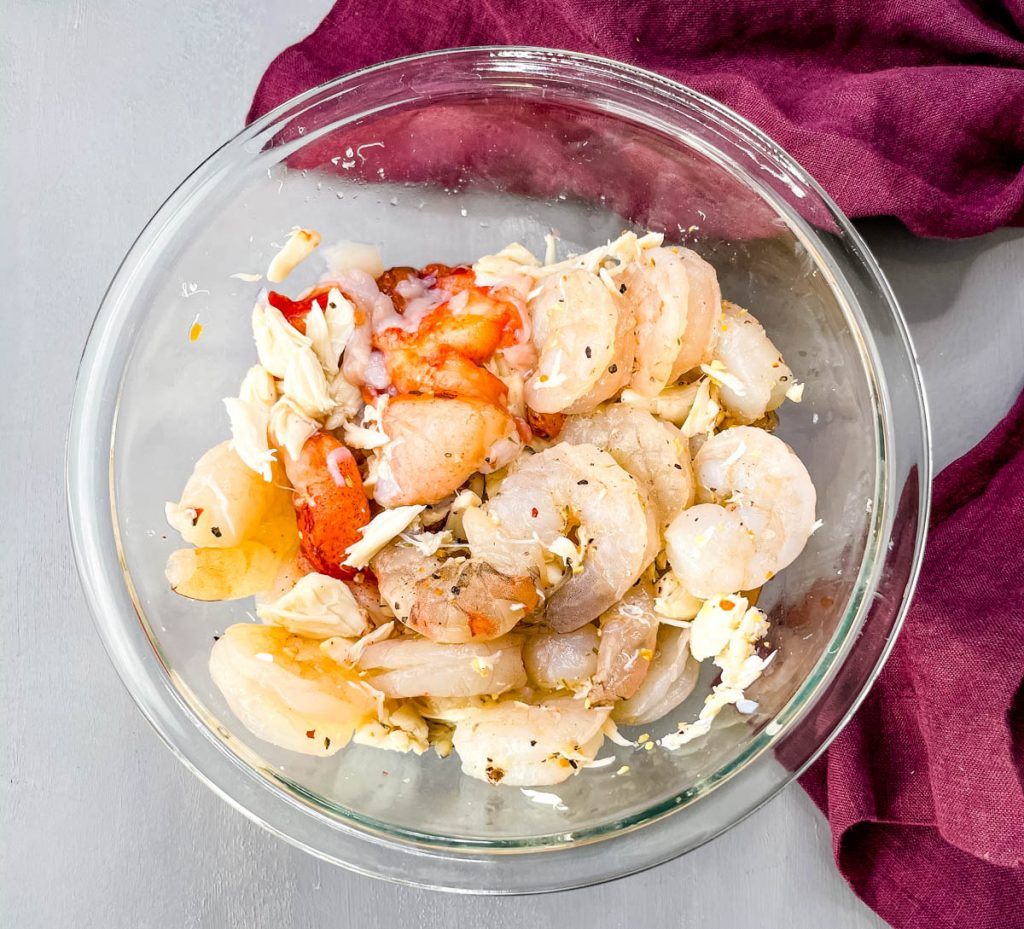 raw seafood shrimp, lobster, and crab in a glass bowl