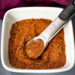 homemade chili seasoning in a white bowl with a spoon