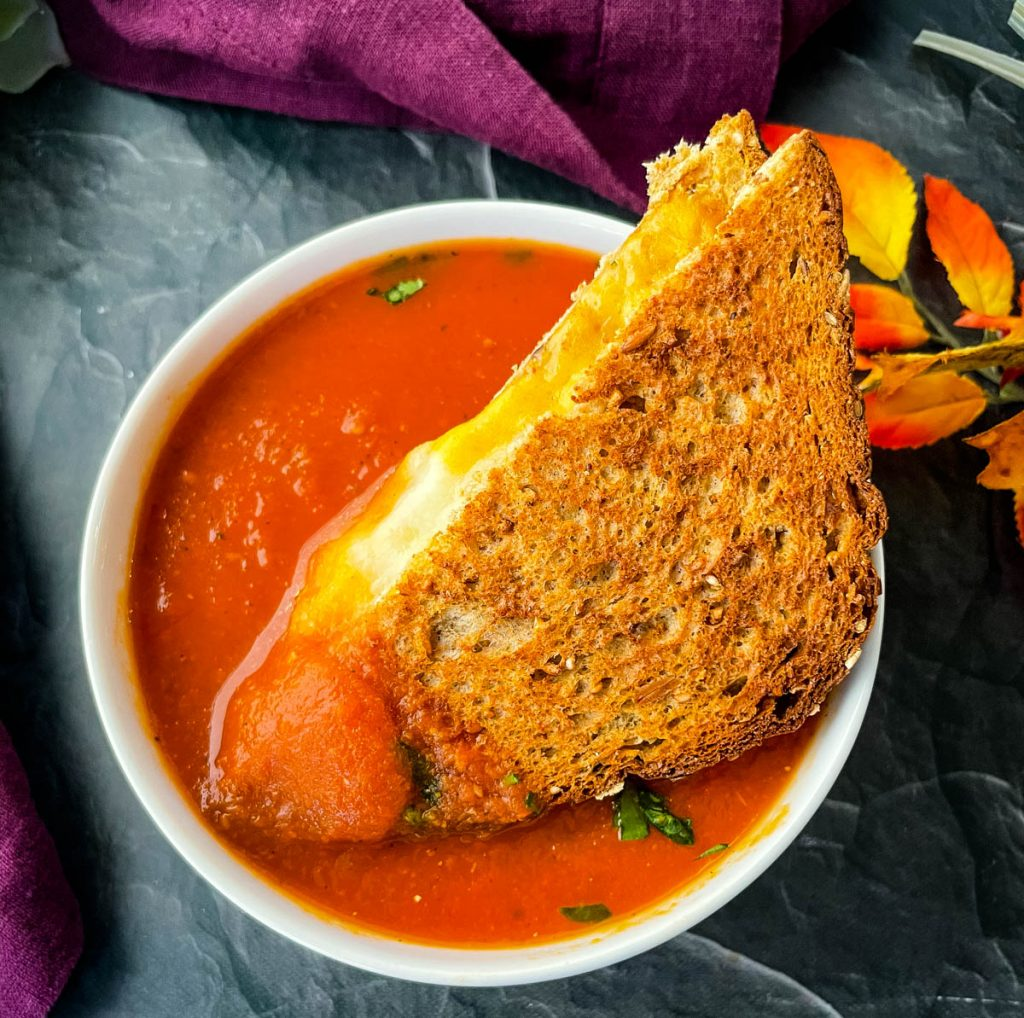 grilled cheese sandwich in a bowl of tomato soup