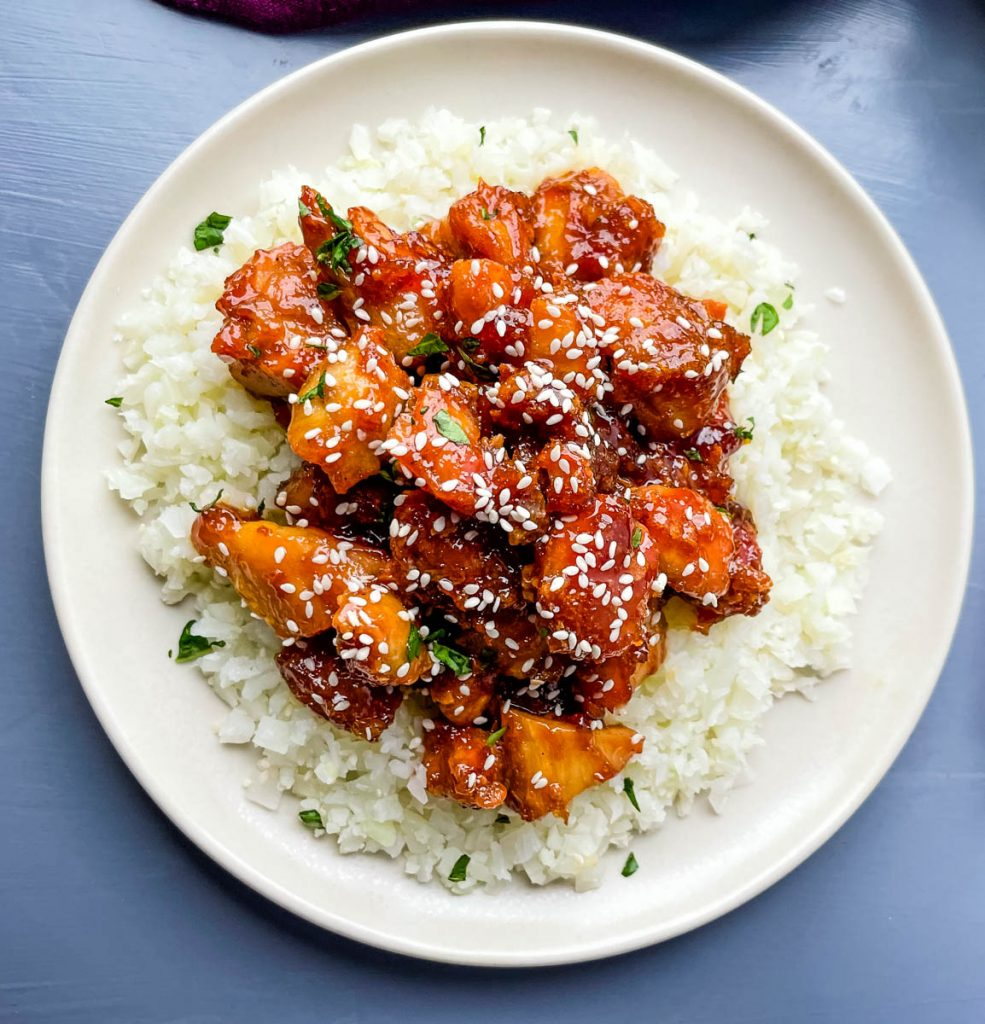 keto low carb orange chicken on a white plate with sesame seeds