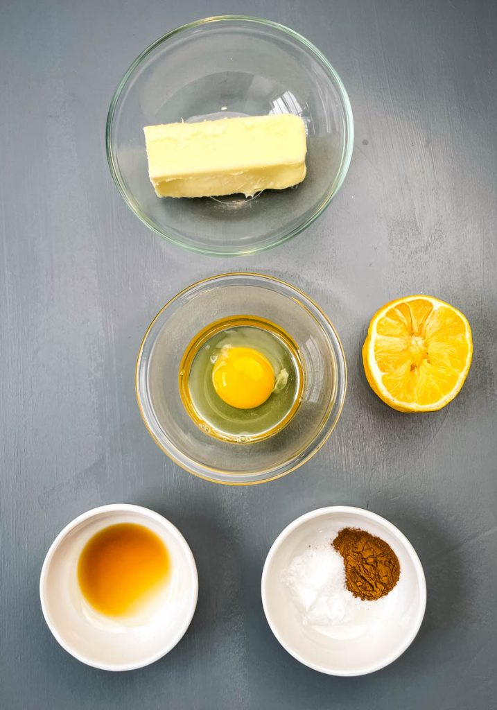 butter, raw egg, lemon, vanilla extract, and cinnamon on a flat surface