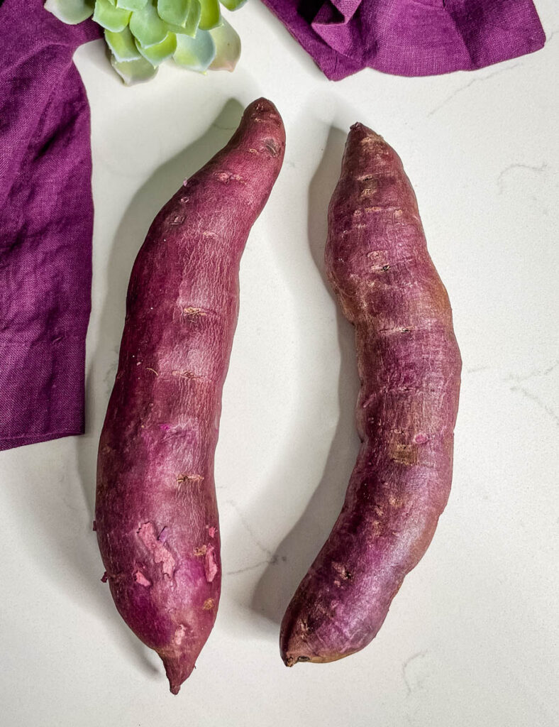 raw Stokes purple sweet potato on a flat surface