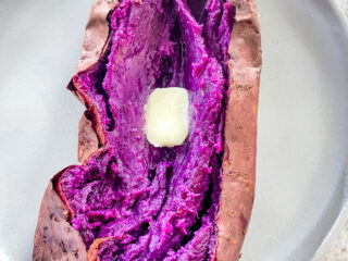 Stokes purple sweet potato fully cooked and sliced open on a plate with buter