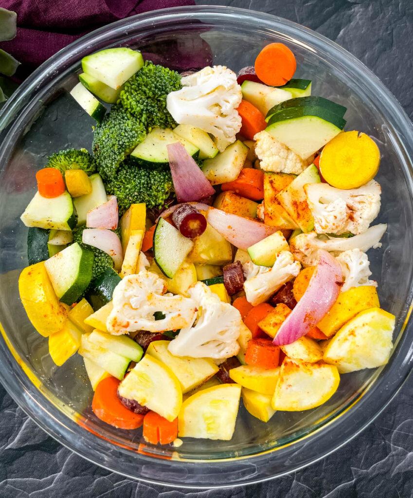 squash, zucchini, onions, carrots, broccoli, and cauliflower in a glass bowl