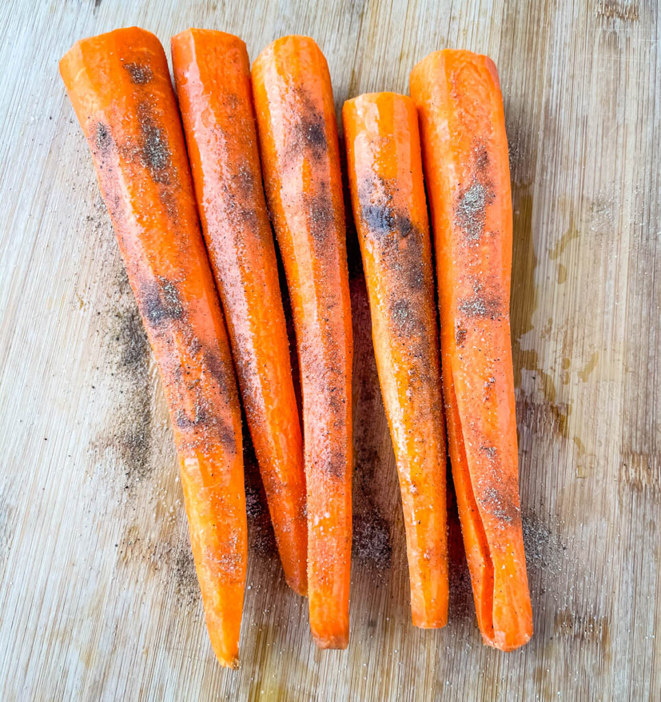 raw carrots seasoned with spices on a cutting board