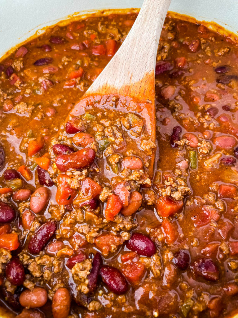 a wooden spoonful of beef chili in a Dutch oven