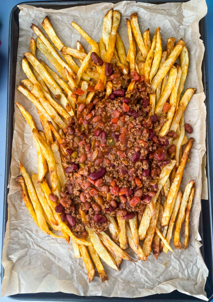 cooked French fries on a sheet pan with chili