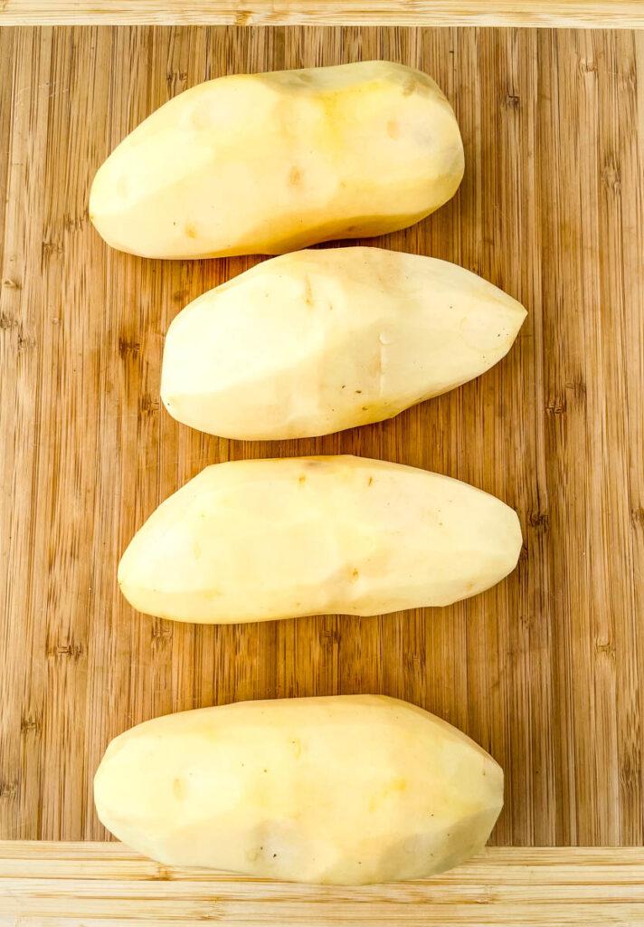 raw russet potatoes peeled on a bamboo cutting board