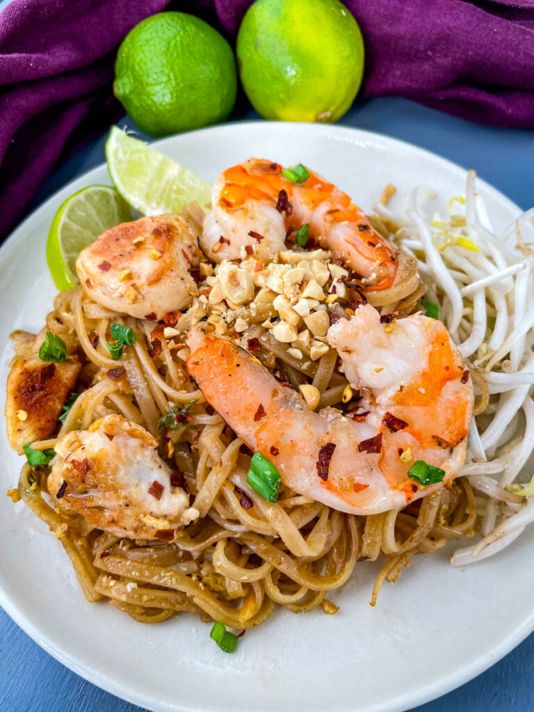 healthy pad thai with chicken, shrimp, bean sprouts, and lime on a white plate