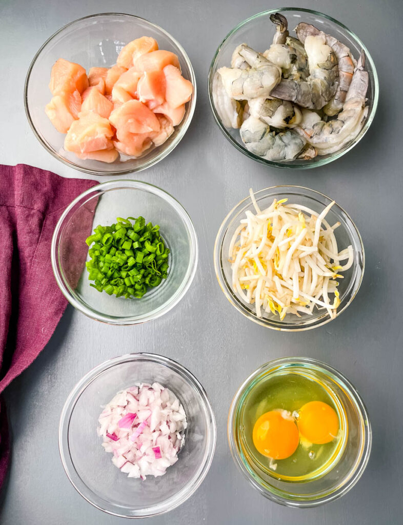raw chicken, raw shrimp, chopped green onions, bean sprouts, chopped onions, and raw eggs in separate glass bowls
