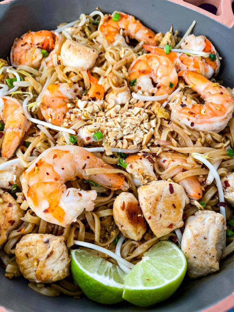healthy pad thai with chicken, shrimp, bean sprouts, and lime in a pan