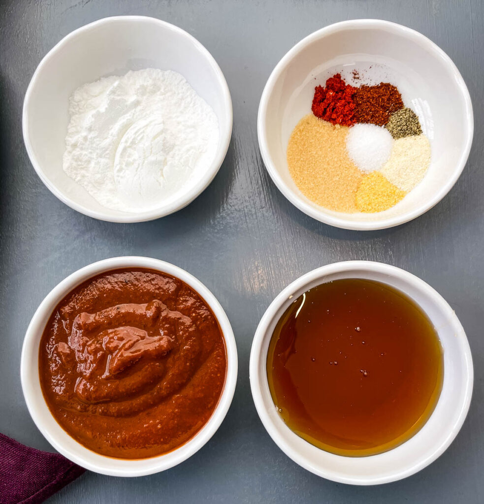 baking powder, BBQ rub, maple syrup, and BBQ sauce in separate white bowls