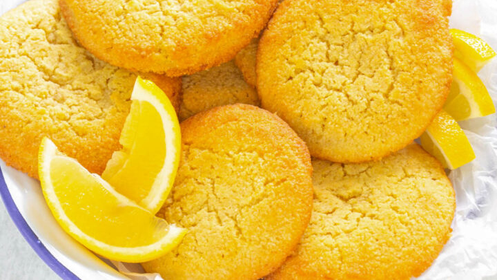 keto low carb lemon cookies on.a white plate with lemon wedges