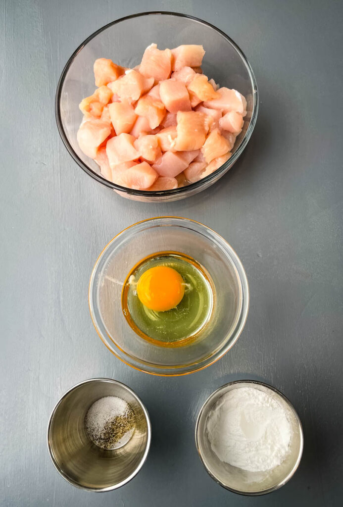 raw sliced chicken, raw egg, soy sauce, salt and pepper in separate bowls