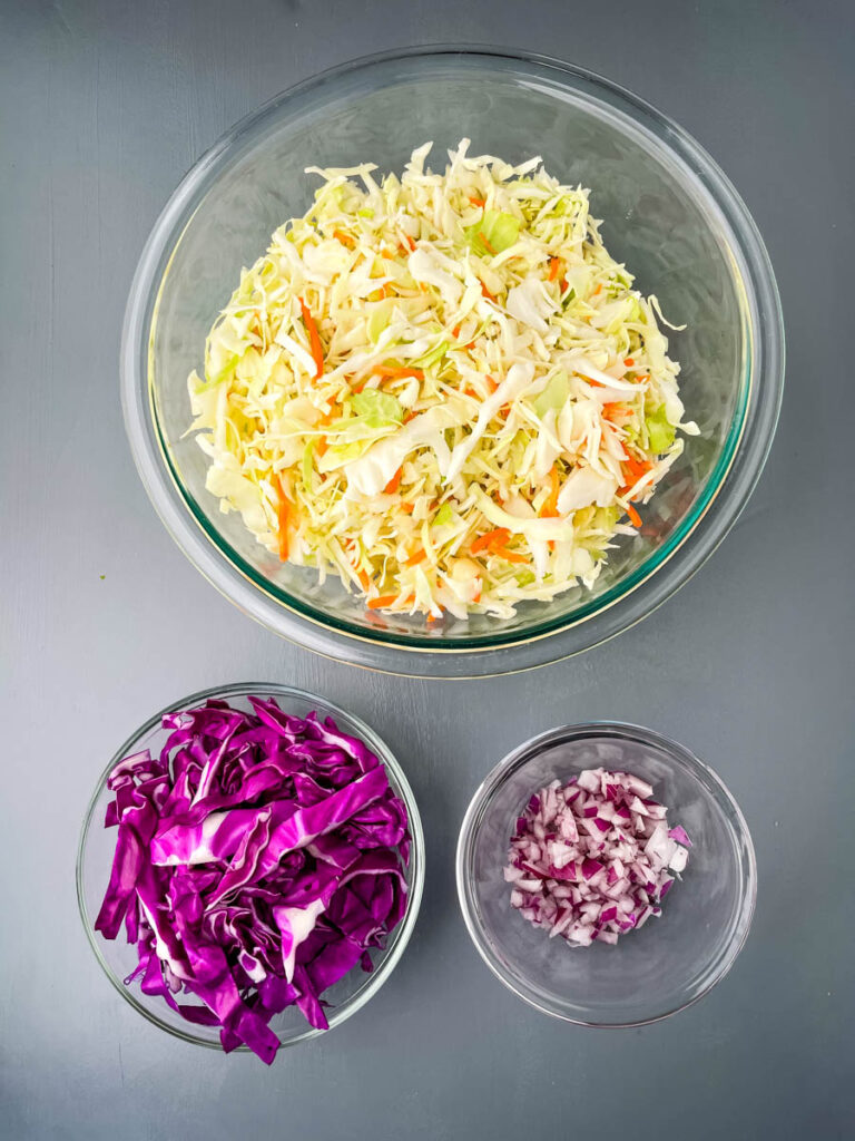 fresh coleslaw mix, red cabbage, onions in glass bowls