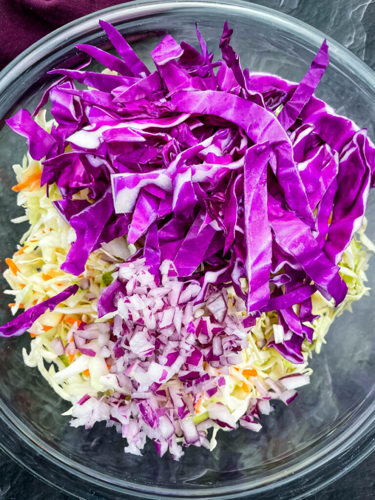 red cabbage, coleslaw mix, and chopped onions in a glass bowl