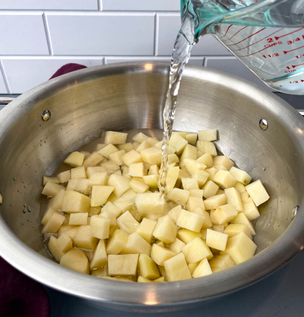 water poured into a pot with sliced potatoes