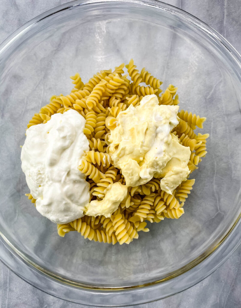 cooked rotini pasta in a glass bowl with mayo and greek yogurt