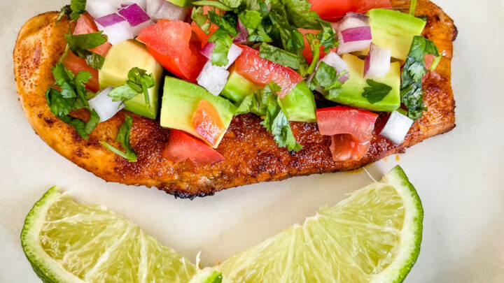 cooked chicken and avocado salsa on a plate with limes