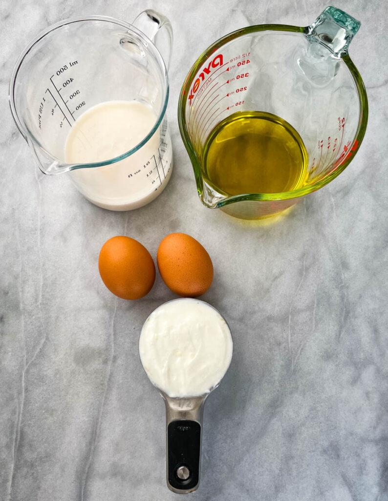 milk, olive oil, eggs, and Greek yogurt in separate bowls
