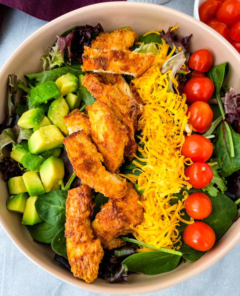 fried chicken salad in a pink bowl with avocado, tomatoes, and cheese