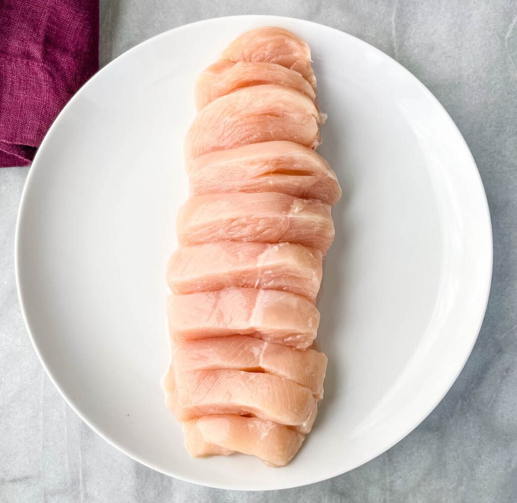 raw sliced chicken breast on a white plate