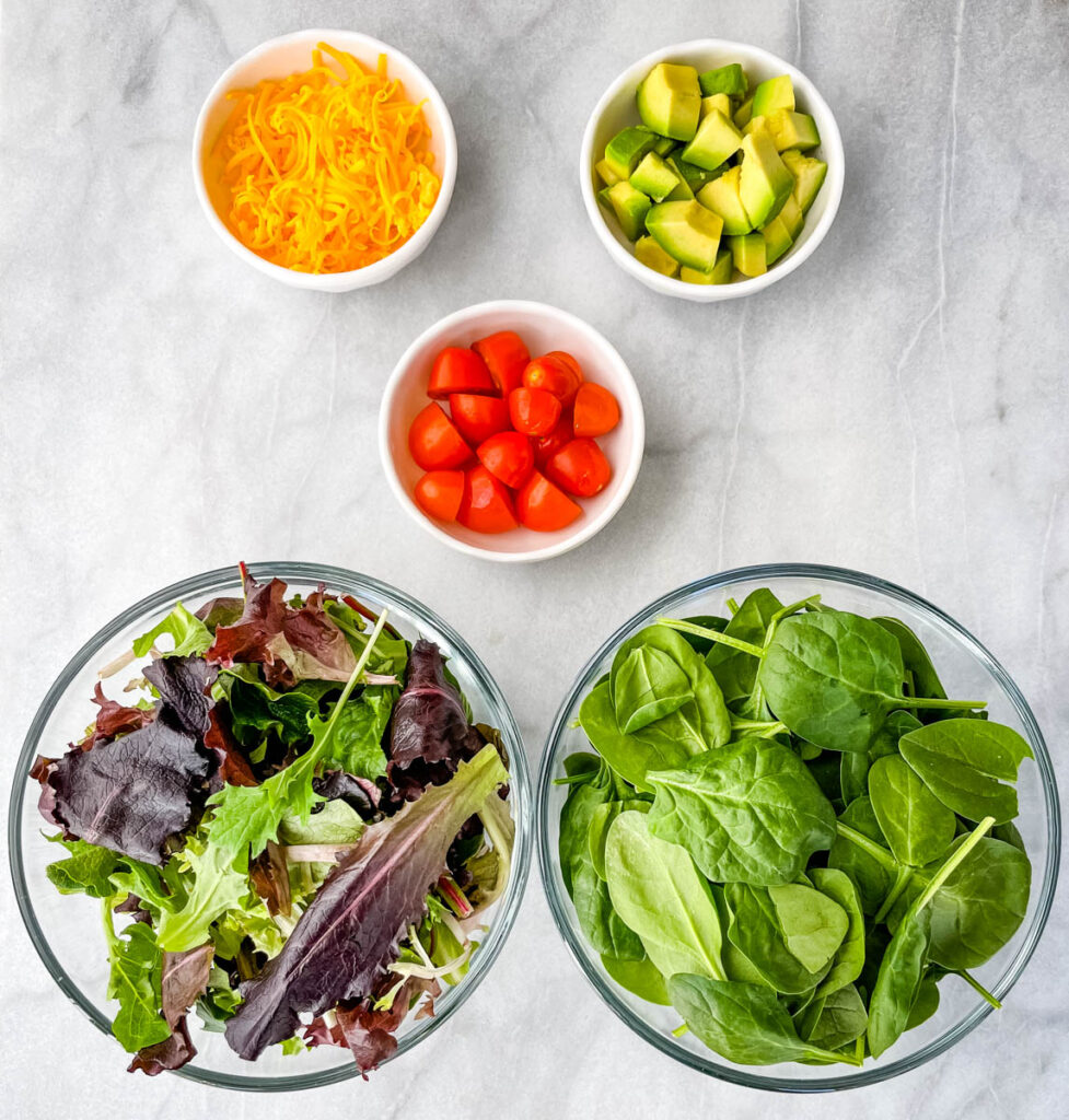 salad greens, spinach, tomatoes, cheddar cheese, avocados, and tomatoes in separate bowls