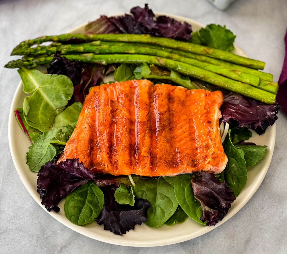 maple glazed salmon on a plate with asparagus and mixed greens