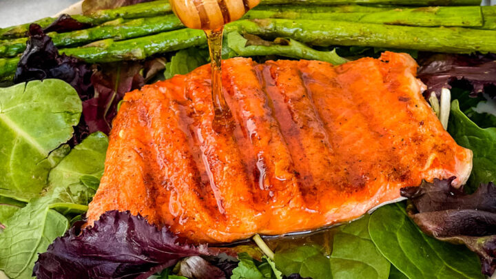 maple glazed salmon drizzled in syrup on a plate with asparagus and mixed greens