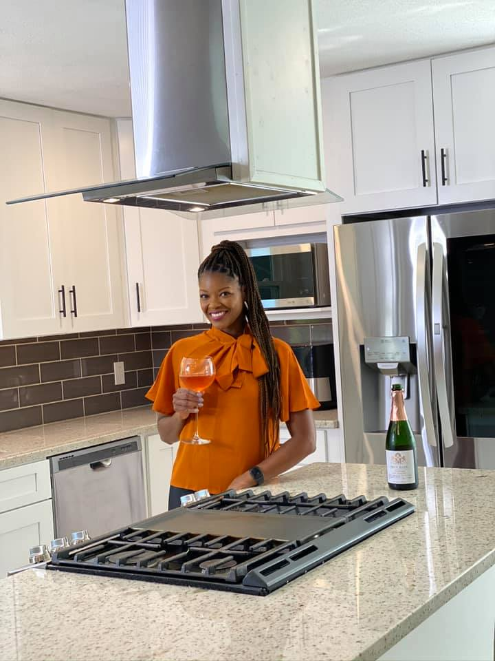person holding wine in a kitchen