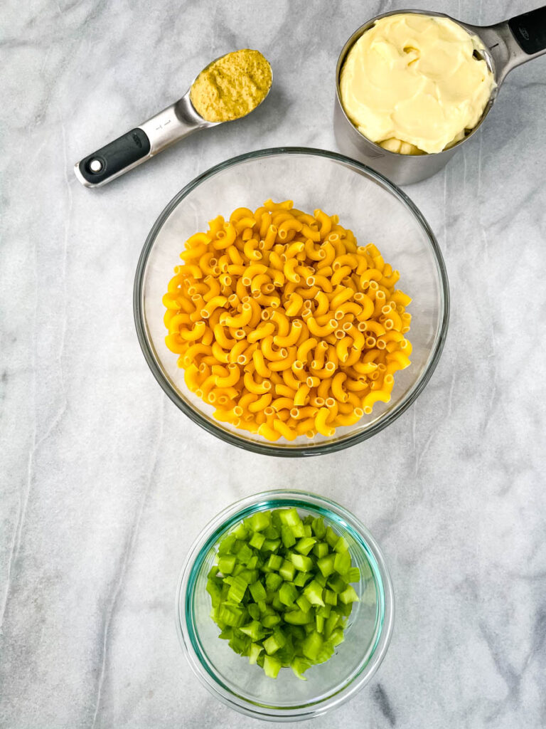 mustard, mayo, uncooked macaroni pasta, and chopped celery in glass bowls