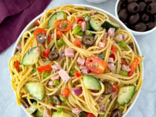 spaghetti salad in a white bowl with tomatoes and olivess
