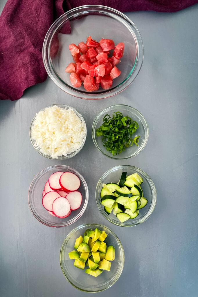 raw ahi tuna, white rice, fresh avocado, fresh radishes, chopped green onions, and cucumbers in separate bowls
