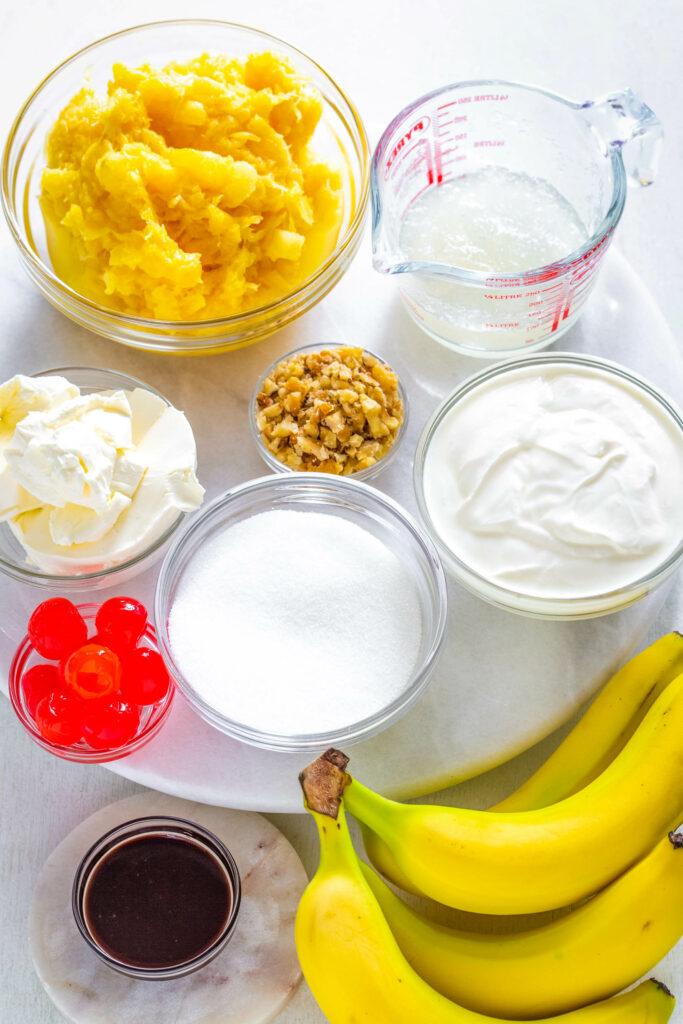 crushed pineapple, cherries, bananas, Greek yogurt, cream cheese, and sweetener in separate bowls