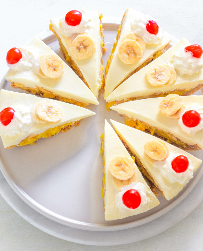 banana split pie on a plate with cherries and whipped cream