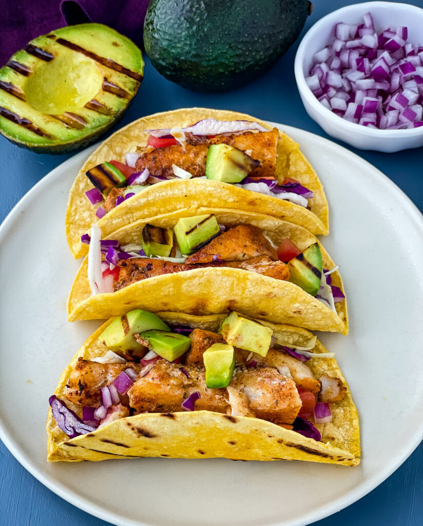 Blackened Fish Tacos on a plate with fresh avocado and cabbage