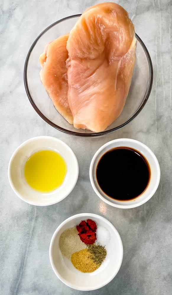 raw chicken breasts, olive oil, balsamic vinegar, and seasonings in separate bowls