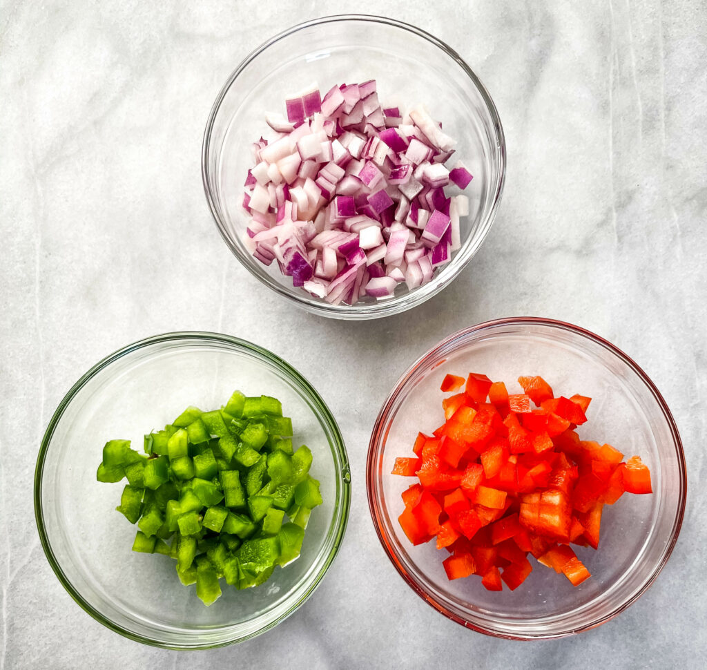 chopped onions, green peppers, and red onions in separate bowls