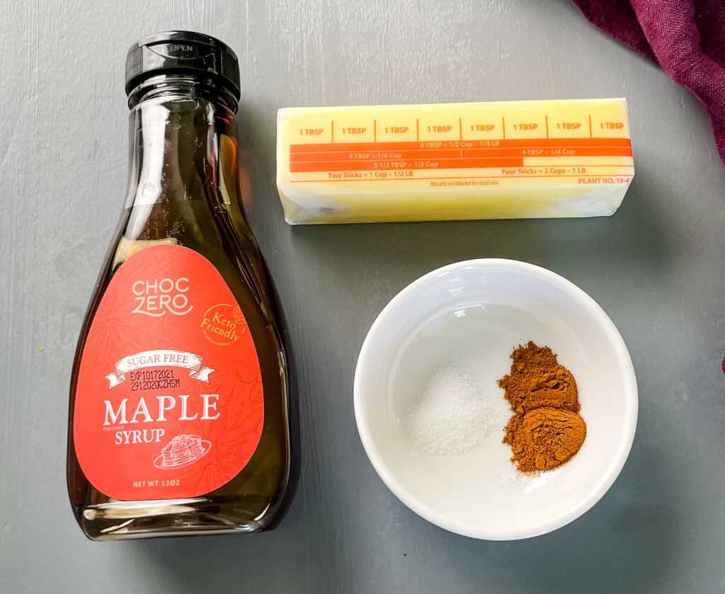 a stick of butter, maple syrup, and cinnamon on a flat surface