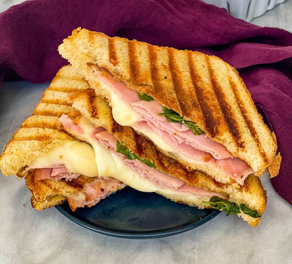 sliced ham and cheese panini sandwich on a plate