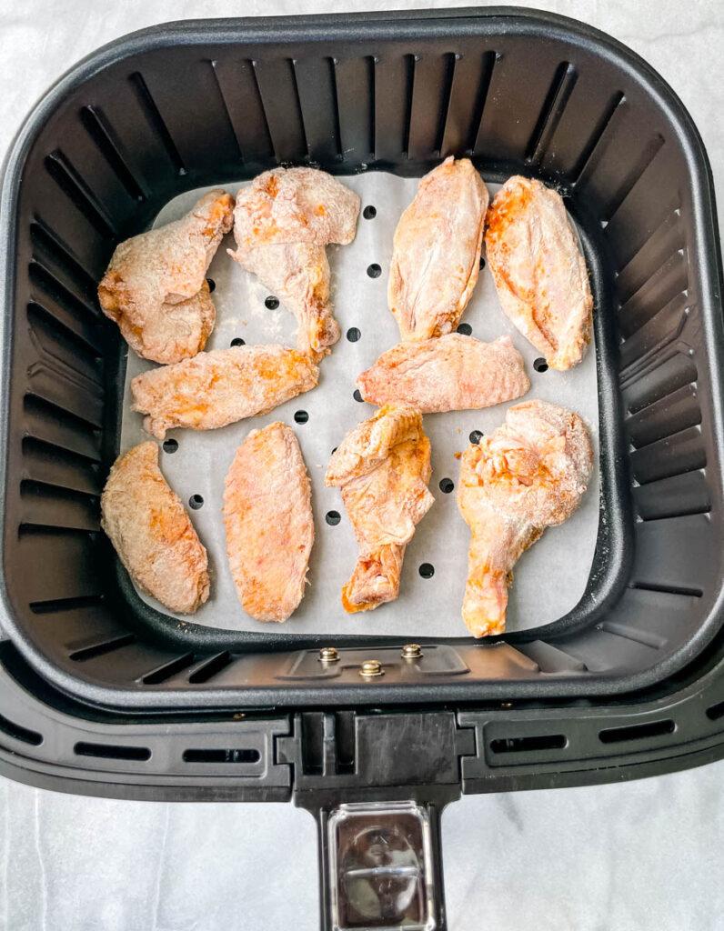 raw breaded chicken wings in a basket