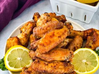 lemon pepper wings on a white plate with fresh lemon