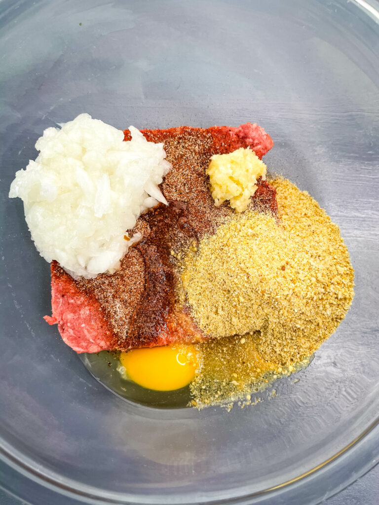 raw ground beef, onions, breadcrumbs, garlic, and an egg in a glass bowl