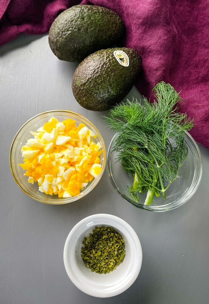 avocados, chopped eggs, and herbs in separate bowls