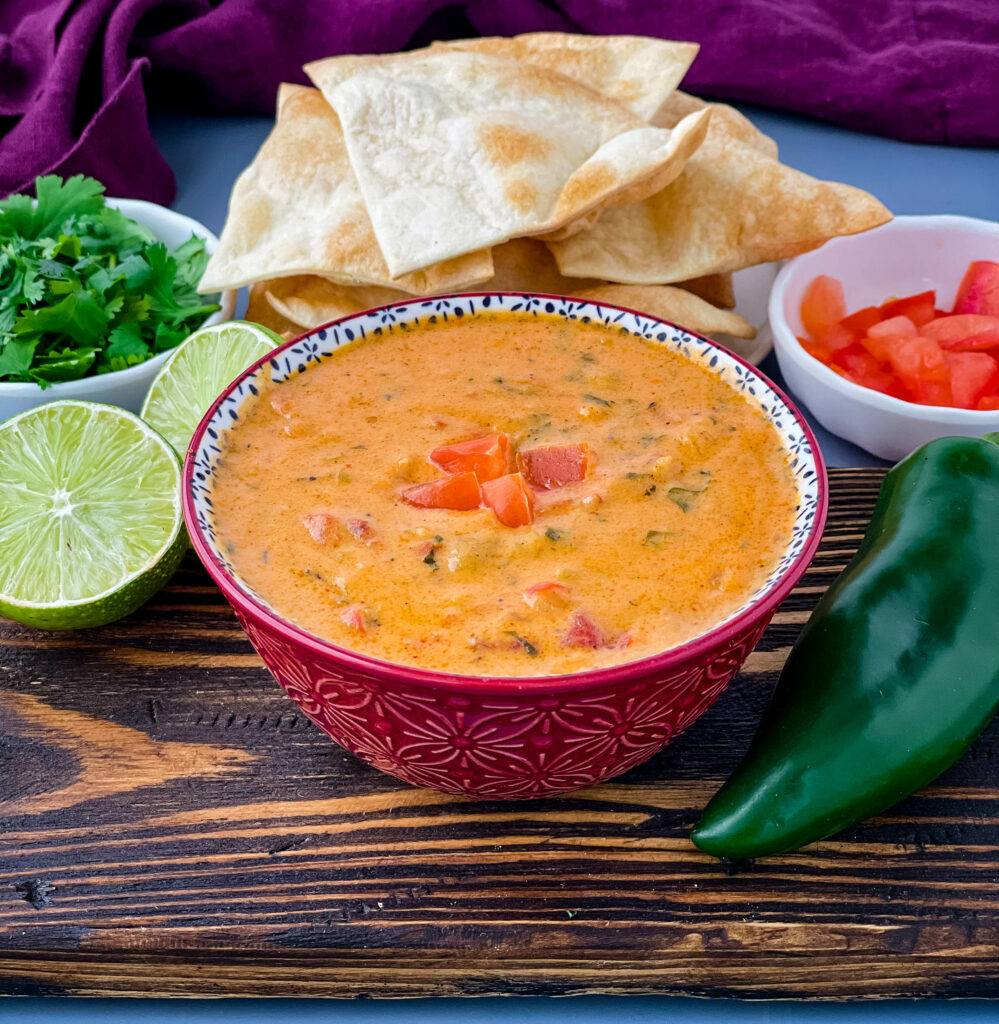 queso cheese dip in a red bowl with a plate of chips