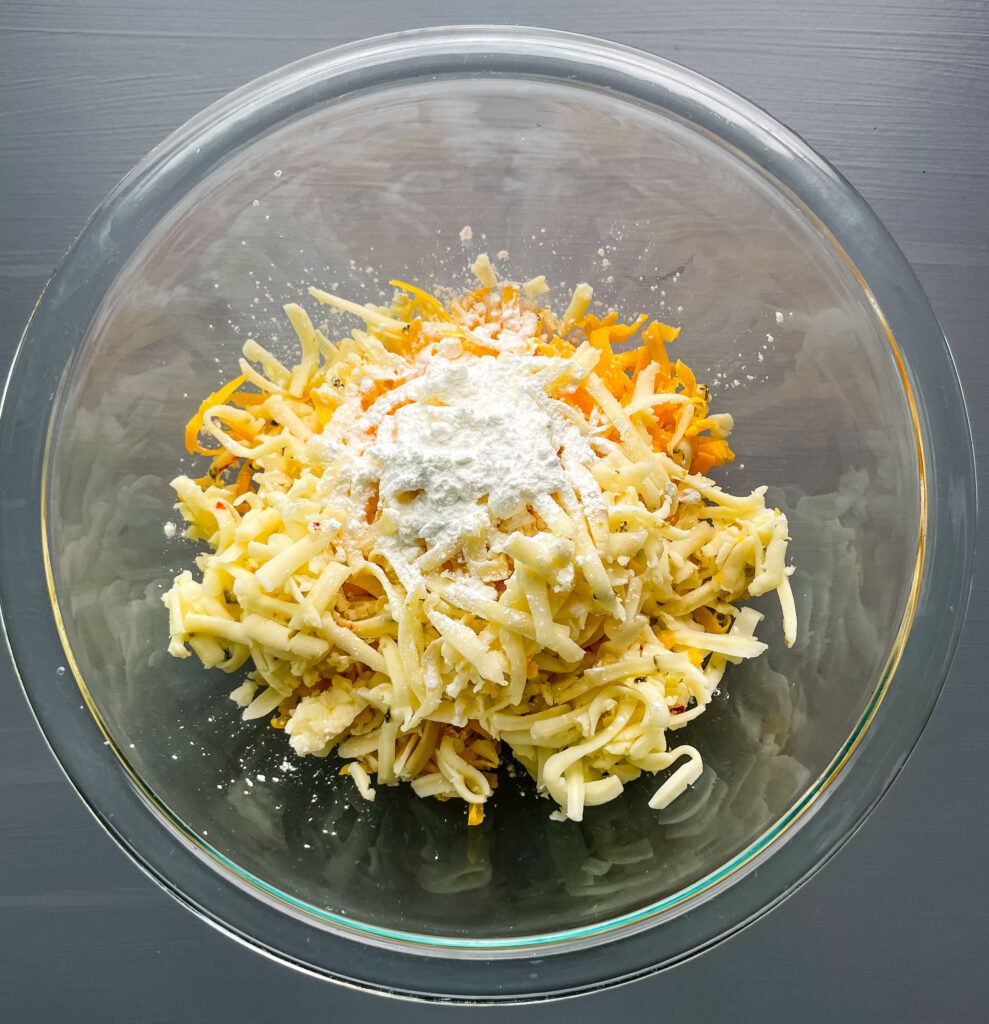 a glass bowl of cheddar cheese and pepper jack cheese