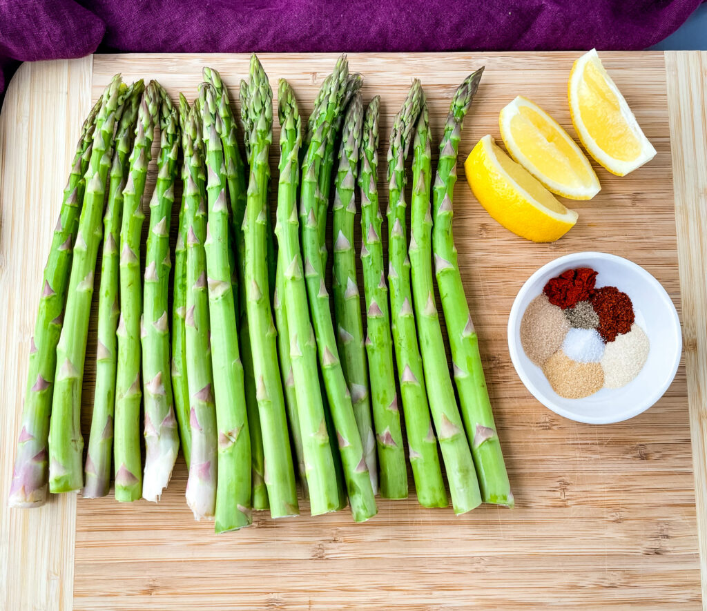 raw asparagus on a wooden cutting board with lemons and bbq seasoning