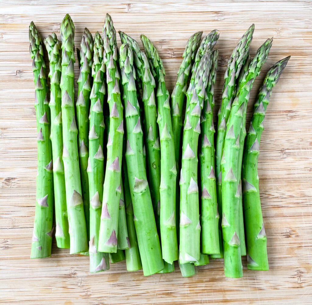 trimmed raw asparagus on a wooden cutting board